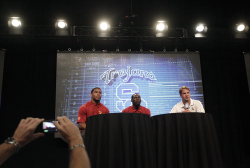 Southern California head coach Lane Kiffin, right, joined by linebacker Hayes Pullard, left, and wide receiver Marqise Lee, talks to the media during the NCAA college football Pac-12 media day on Friday, July 26, 2013, in Culver City, Calif. (AP Photo/Jae C. Hong)