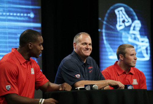 Arizona coach Rich Rodriguez, center, smiles as he is joined by wide receiver Terrence Miller, left, and linebacker Jake Fischer during Pac-12 football media day on Friday, July 26, 2013, in Culver City, Calif. (AP Photo/Jae C. Hong)
