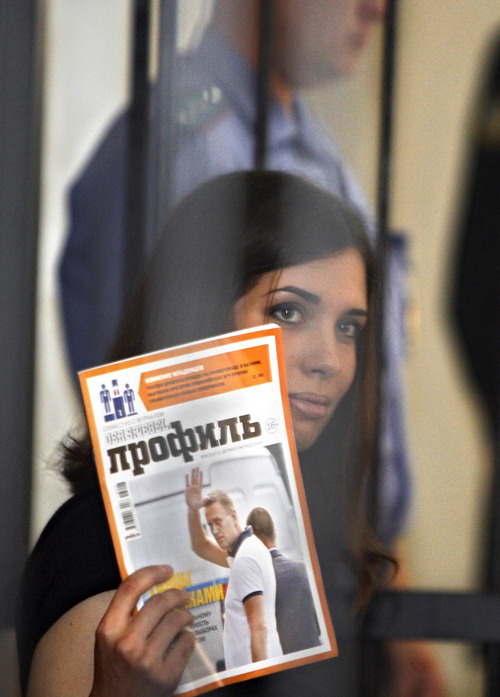 Nadezhda Tolokonnikova, a member of the feminist punk band, Pussy Riot, holds a magazine with a portrait of Russian opposition leader Alexey Navalny, as she sits  behind bars at a district court in Saransk on Friday, July 26, 2013. The court has rejected an appeal by a member of the Russian punk band Pussy Riot against a previous court ruling that denied her an early release. Nadezhda Tolokonnikova has served a year and a half out of her two-year prison sentence and was appealing for parole. Along with two other band members, she was convicted of hooliganism following Pussy Riot's punk performance against President Vladimir Putin in Moscow's main cathedral last year. (AP Photo)