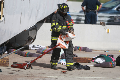 A firefighter spreads clean-up material after a bus crash Saturday, July 27, 2013 in Indianapolis. The Indianapolis Fire Department says three people were killed when a bus carrying teens from a church camp crashed on a busy thoroughfare near Interstate 465. The bus was carrying 40 passengers who are members of Colonial Hill Baptist Church and were returning from camp when the crash happened Saturday afternoon. (AP Photo/The Indianapolis Star, Michelle Pemberton) NO SALES