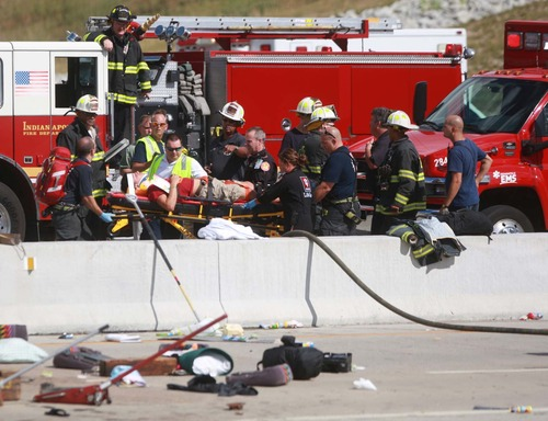 A woman is transported to a helicopter for transport to a hospital after a bus crash, Saturday, July 27, 2013 in Indianapolis. The Indianapolis Fire Department says three people were killed when a bus carrying teens from a church camp crashed on a busy thoroughfare near Interstate 465. The bus was carrying 40 passengers who are members of Colonial Hill Baptist Church and were returning from camp when the crash happened Saturday afternoon. (AP Photo/The Indianapolis Star, Michelle Pemberton) NO SALES