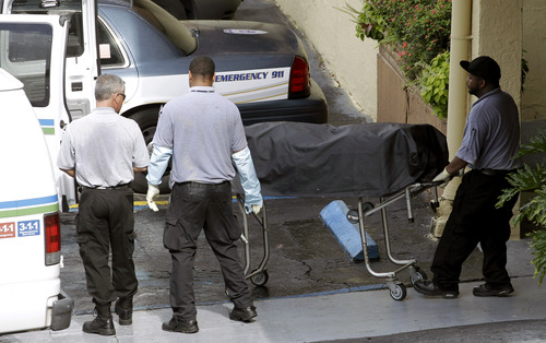 Alan Diaz  |  The Associated Press Miami-Dade morgue workers carry out a body out at the scene of a fatal shooting in Hialeah, Fla., on Saturday. A gunman holding hostages inside the apartment complex killed six people before being shot to death by a SWAT team that stormed the building early Saturday following an hours-long standoff, police said.