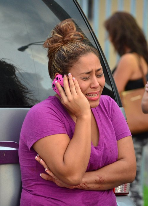 A woman talks on the phone outside an apartment building at the scene of a fatal shooting in Hialeah, Fla., early Saturday, July 27, 2013. A gunman holding hostages inside the apartment complex killed six people before being shot to death by a SWAT team that stormed the building early Saturday following an hours-long standoff, police said. (AP Photo/El Nuevo Herald, Gaston DeCardenas)