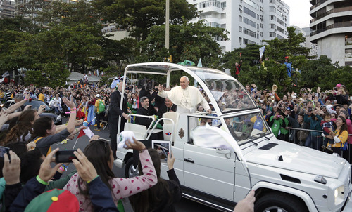 Pope Francis waves to people from his popemobile along the Copacabana beachfront as he arrives for the Stations of the Cross procession in Rio de Janeiro, Brazil, Friday, July 26, 2013. Also known as the Way of the Cross, Via Crucis and Via Dolorosa, the Stations of the Cross are built around reflections on Jesus' last steps leading up to his crucifixion and death.  (AP Photo/Andre Penner)