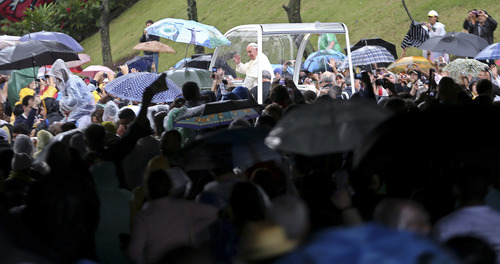 Pope Francis waves to people from his popemobile in Rio de Janeiro, Brazil, Saturday, July 27, 2013. Pope Francis on Saturday challenged bishops from around the world to get out of their churches and preach, and to have the courage to go to the farthest margins of society to find the faithful. (AP Photo/Andre Penner)