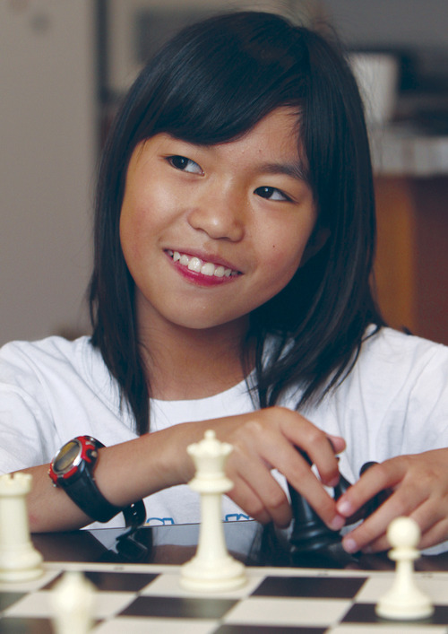 In this July 9, 2013 photo,  Carissa Yip, 9, pauses as she plays a chess match with her father Percy Yip at their home in Chelmsford, Mass. Only three years or so since first picking up the game, Carissa has risen so far up the rankings that she has reached the expert level at a younger age than anyone since the chess federation began electronic record-keeping in 1991.  (AP Photo/The Sun of Lowell, Julia Malakie)