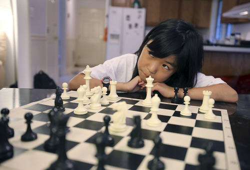 In this July 9, 2013 photo, Carissa Yip, 9, waits for her father Percy Yip to make a move during a chess match at their home in Chelmsford, Mass. Only three years or so since first picking up the game, Carissa has risen so far up the rankings that she has reached the expert level at a younger age than anyone since the chess federation began electronic record-keeping in 1991.  (AP Photo/The Sun of Lowell, Julia Malakie)