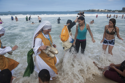 Nuns wade in the Copacabana beach water, in Rio de Janeiro, Brazil, Sunday, July 28, 2013. Pope Francis wrapped up a historic trip to his home continent Sunday with a Mass on the Copacabana beachfront  that drew a reported 3 million people. (AP Photo/Nicolas Tanner)