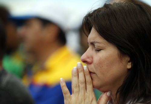 A woman prays during the World Youth Day's closing Mass celebrated by Pope Francis on the Copacabana beachfront in Rio de Janeiro, Brazil, Sunday, July 28, 2013. An estimated 3 million people poured onto Rio's Copacabana beach on Sunday for the final Mass of Pope Francis' historic trip to his home continent, cheering the first Latin American pope in one of the biggest turnouts for a papal Mass in recent history. (AP Photo/Silvia Izquierdo)