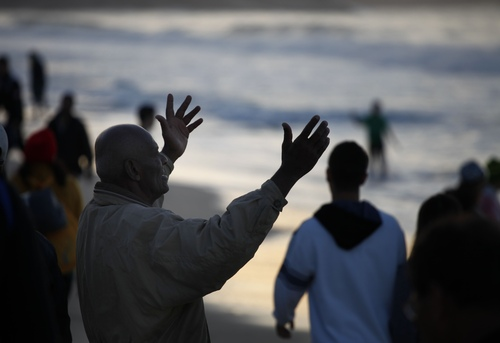 A pilgrim prays early morning after a vigil in Copacabana beach in Rio de Janeiro, Brazil, Sunday, July 28, 2013.Hundreds of thousands of young people slept under chilly skies in the white sand awaiting Pope Francis' final Mass for World Youth Day.(AP Photo/Jorge Saenz)