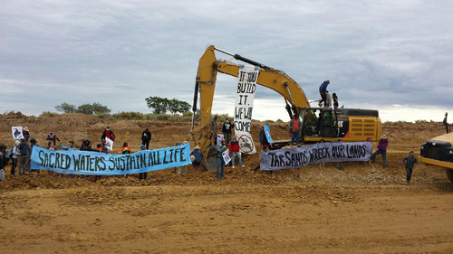 | Steve Liptay/Peaceful Uprising Protesters on Monday stopped work on a road to serve a tar sands mine in the Uinta Basin, some of them duct taping themselves to heavy machinery.