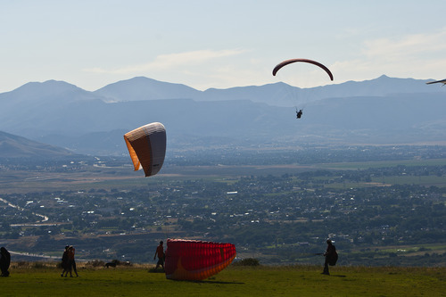 Chris Detrick  |  The Salt Lake Tribune With pollution visible in the background, paragliders fly over Point of the Mountain Flight Park at Steep Mountain near Geneva Rock Products in Draper Friday July 19, 2013.
