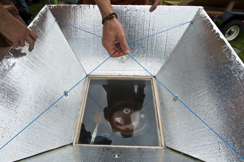 Chris Detrick  |  The Salt Lake Tribune Jason Schulz, of Salt Lake City, looks at a solar cooker during Solar Day at Liberty Park Saturday July 27, 2013.