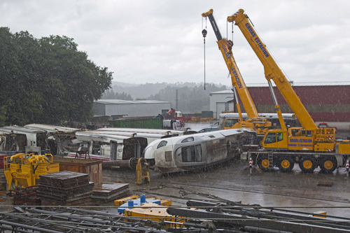 Part of the wreckage of the crashed train is seen in a crane depository on the outskirts of Santiago de Compostela, Spain, Sunday July 28, 2013. Spain's interior minister Jorge Fernandez Diaz says the driver whose speeding train crashed, killing 78 people, is now being held on suspicion of negligent homicide. The Spanish train derailed at high speed Wednesday killing and injuring dozens. (AP Photo/Lalo R. Villar)