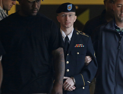 FILE - In this Monday, July 29, 2013, file photo, Army Pfc. Bradley Manning is escorted to a security vehicle outside of a courthouse in Fort Meade, Md. U.S. Army Pfc. Bradley Manning was acquitted Tuesday, July 30, 2013, of aiding the enemy for giving classified secrets to WikiLeaks. The military judge hearing the case, Army Col. Denise Lind, announced the verdict. (AP Photo/Patrick Semansky, File)