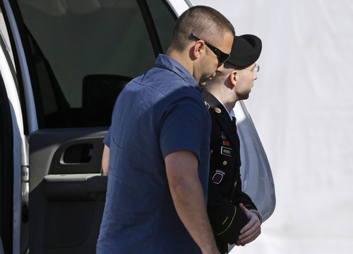 Army Pfc. Bradley Manning, right, is escorted into a courthouse in Fort Meade, Md., Tuesday, July 30, 2013, before a hearing in his court martial. The military judge hearing Manning's trial is expected to announce her decision Tuesday afternoon. Manning faces 21 counts including espionage, computer fraud and theft charges, but the most serious is aiding the enemy, which carries a possible life sentence. (AP Photo/Patrick Semansky)