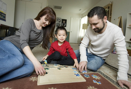 Paul Fraughton     The Salt Lake Tribune Stephanie and Harlan McCoy play with their adopted son Gabe in their Saratoga Springs home.  Tuesday, February 5, 2013