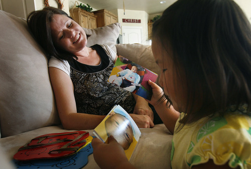 Scott Sommerdorf      The Salt Lake Tribune Julie Anderegg talks with Lizzie as she looks through some photos of Ellie Mei Jie in the Anderegg's Lehi home, Friday, July 26, 2013. The Andereggs are in the process of adopting their second child, Ellie Mei Jie, from China. As they did the first time, the Lehi couple are using crowdfunding to help cover adoption costs.