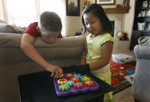 Scott Sommerdorf   |  The Salt Lake Tribune Older brother Nathan Anderegg, 9, plays with Lizzie, right, Friday, July 26, 2013. The Andereggs are in the process of adopting a second child Ellie Mei - from China. As they did the first time, the Lehi couple are using crowdfunding to help cover adoption costs.