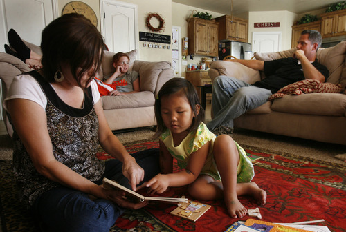 Scott Sommerdorf   |  The Salt Lake Tribune Julie Anderegg reads with Lizzie in the Anderegg's Lehi home, Friday, July 26, 2013. The Andereggs are in the process of adopting a second child - Ellie Mei - from China. As they did the first time, the Lehi couple are using crowdfunding to help cover adoption costs. In the background, Jacob Anderegg,  right talks with one of his three biological children, Joshua, second from left.