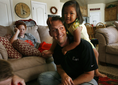 Scott Sommerdorf   |  The Salt Lake Tribune Lizzie climbs onto her adopted father's shoulders as Representative Jacob Anderegg plays with Lizzie and one of his three biological children, Nathan, left, in their Lehi home, Friday, July 26, 2013. The Andereggs are in the process of adopting a second child - Ellie Mei Jie - from China. As they did the first time, the Lehi couple are using crowdfunding to help cover adoption costs.