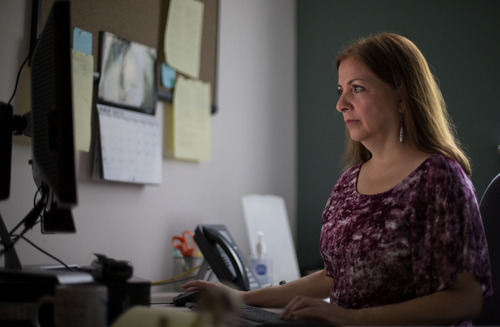 Lori Marino, a lecturer in psychology at Emory University who has conducted extensive research on the intelligence of whales, dolphins and primates, works in her office, Friday, July 26, 2013, in Atlanta. There's extensive evidence that pigs are as smart and sociable as dogs. Yet one species is afforded affection and respect, while the other faces mass slaughter en route to becoming bacon, ham and pork chops. Seeking to capitalize on that discrepancy, animal-welfare advocates are launching a campaign called The Someone Project that aims to depict pigs, chickens, cows and other farm animals as more intelligent and emotionally complex than is commonly believed. The hope is that increasing numbers of Americans might view these animals with the same empathy that they view dogs, cats, elephants, great apes and dolphins. (AP Photo/David Goldman)