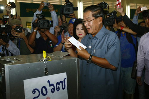 Cambodia's Prime Minister Hun Sen, center, casts his ballot at a polling station in Takhmau town, south of Phnom Penh, Cambodia, Sunday, July 28, 2013. Cambodians began voting across the country Sunday to take part in what has become a familiar ritual - the re-election of Prime Minister Hun Sen, who has been on the job for 28 years and says he hopes to rule for at least another decade. (AP Photo/Heng Sinith)