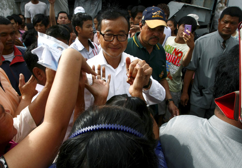 Sam Rainsy, center, leader of Cambodia National Rescue Party greets villagers while visiting a polling station at Chak Angre Leu pagoda, in Phnom Penh, Cambodia, Sunday, July 28, 2013. Cambodians began voting across the country Sunday to take part in what has become a familiar ritual - the re-election of Prime Minister Hun Sen, who has been on the job for 28 years and says he hopes to rule for at least another decade. (AP Photo/Heng Sinith)