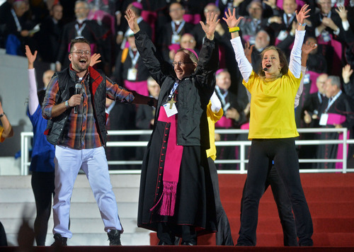"""An unidentified clergy member dances with performers before the start of a vigil on Copacabana beach in Rio de Janeiro, Brazil, Saturday, July 27, 2013.  Pope Francis drew faithful to Rio's Copacabana beach on Saturday for the final evening of World Youth Day, hours after he chastised the Brazilian church for failing to stem the """"exodus"""" of Catholics to evangelical congregations. (AP Photo/Luca Zennaro, Pool)"""