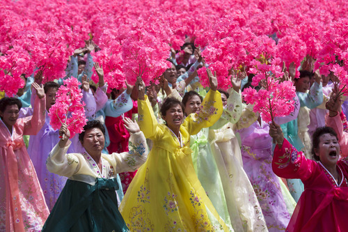 North Korean women wave to their leader Kim Jong Un during a mass military parade on Kim Il Sung Square in Pyongyang to mark the 60th anniversary of the Korean War armistice Saturday, July 27, 2013. (AP Photo/David Guttenfelder)