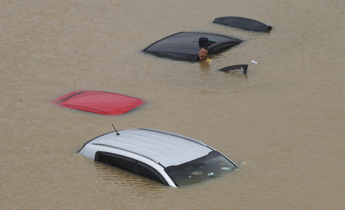 A man struggles to move a vehicle submerged in floodwater after torrential rainfall hit the metropolitan area in Seoul, South Korea, Monday, July 22, 2013. Heavy rain battered the central part of the Korean Peninsula, including Seoul and its vicinities, Monday, flooding homes and roads, according to police. (AP Photo/Ahn Young-joon)