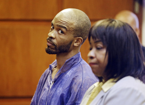 Michael Madison glances at court-appointed attorney Marlene Rideenour during his arraignment in East Cleveland on Monday, July 22, 2013. Madison has been charged with aggravated murder in the deaths of three women found in garbage bags in the city over the weekend. (AP Photo/Mark Duncan)