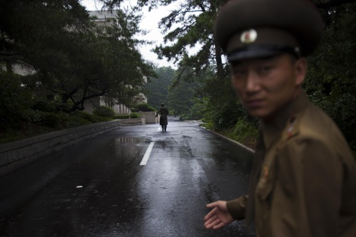 North Korean soldiers walk along a road in front of the truce village of Panmunjom at the Demilitarized Zone (DMZ) which separates the two Koreas on Monday, July 22, 2013. (AP Photo/David Guttenfelder)