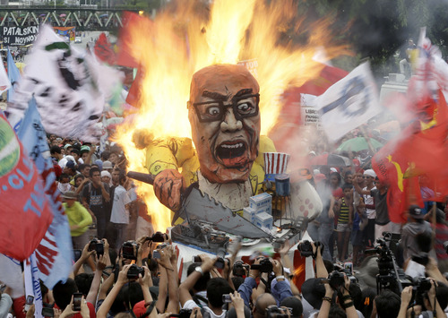 Protesters burn an effigy of Philippine President Benigno Aquino III during a rally to coincide with his fourth State-of-the-Nation Address (SONA) before the country's congressmen and senators Monday July 22, 2013 at the House of Representatives at suburban Quezon city, northeast of Manila, Philippines. President Aquino III is expected to dwell on the gains of his administration particularly on the robust economy but the protesters see otherwise especially on the increasing prices of oil and basic services as water and electricity. (AP Photo/Bullit Marquez)