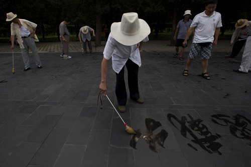 Elderly Chinese men practice writing calligraphy using a brush and water on stone pavements at a park in Beijing, China, Monday, July 22, 2013. (AP Photo/Ng Han Guan)