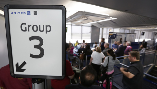 "In this photo taken May 8, 2013, in Chicago, groups of passengers wait at a United Airlines gate to board a flight in separate numbered lanes at O'Hare International Airport. Industry wide boarding passengers on flights vacillates between a social science and a financial quandary. There's an economic cost for airlines that run late. Researchers from Northern Illinois University said that at one major airline, which they didn't identify, said every extra minute at the gate costs $30. To cut overhead, United reduced the number of boarding groups from seven to five while adding lanes in gate areas _ from two to five at big airports. That's designed to eliminate ""gate lice"" _ the name road warriors use for those anxious passengers with big carry-ons who cause a traffic jam by creeping forward long before their group is called. (AP Photo/M. Spencer Green)"