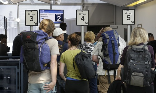 In this photo taken May 8, 2013, groups of passengers wait at a United Airlines gate to board a flight in separate numbered lanes at O'Hare International Airport in Chicago. For airlines, every minute that a plane sits at the gate makes it more likely that the flight will be late, hurting the carrier's on-time rating and causing passengers to miss connecting flights. But the perfect boarding process remains elusive. Even an astrophysicist couldn't figure it out. (AP Photo/M. Spencer Green)
