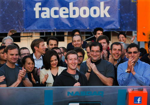 FILE - In this May 18, 2012 file photo provided by Facebook, Facebook founder, Chairman and CEO Mark Zuckerberg, center, rings the Nasdaq opening bell from Facebook headquarters in Menlo Park, Calif. Facebook's stock has passed its IPO price of $38 before the market open on Wednesday, July 31, 2013. If the gains hold in the regular session, it would mark the first time the stock has risen above that mark since its rocky initial public offering in May 2012. Menlo Park-based Facebook has been on a roll since it reported stronger-than-expected earnings on July 24. Investors are upbeat about its fast-growing mobile advertising revenue. (AP Photo/Nasdaq via Facebook, Zef Nikolla, File)