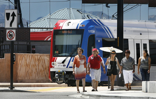 Scott Sommerdorf  |  Tribune file photo A family on its way to shop across the street at the Valley Fair Mall, passes by a TRAX train as it leaves the West Valley Central Station in August 2011. Ridership numbers on that line have thus far risen to only 80 percent of UTA's projections.