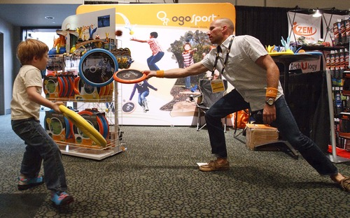 Leah Hogsten  |  The Salt Lake Tribune Ogo Sport rep Matthew Roman tosses Ogo toys at the OR show Wednesday, July 31, 2013, with Fausto Delfin, who just wandered over to Roman's booth to play with the merchandise. More than 27,000 attendees peruse the aisles of the Outdoor Retailer's 2013 Summer Market at the the Salt Palace Convention Center Wednesday during Salt Lake City's biggest convention.