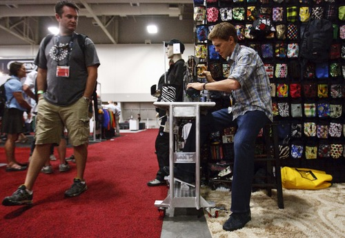 Leah Hogsten  |  The Salt Lake Tribune Sam Krieg, owner and tailor of Krieg bags from Pocatello, Idaho, sews climbing chalk bags and bicycle bags at the OR show Wednesday, July 31, 2013. More than 27,000 attendees peruse the aisles of the Outdoor Retailer's 2013 Summer Market at the the Salt Palace Convention Center Wednesday during Salt Lake City's biggest convention.