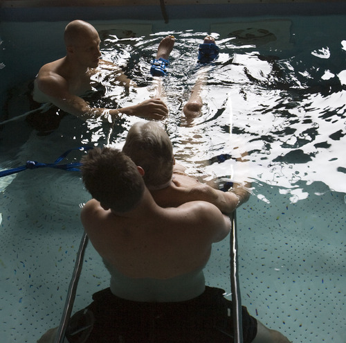 Steve Griffin  |  The Salt Lake Tribune   Brooke Hopkins, who was paralyzed from a bicycle accident three years ago, works with physical therapists Matt Hansen and Mike Erickson during pool therapy at Neuroworx in South Jordan, Utah Friday, November 11, 2011.