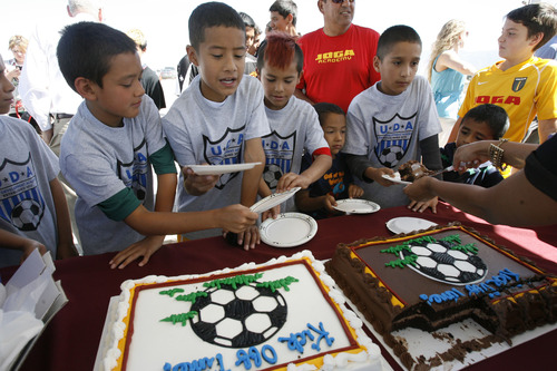 Francisco Kjolseth  |  The Salt Lake Tribune Young soccer members of the Utah Development Academy are finally rewarded with cake after standing through speeches by Mayor Ralph Becker, City Councilman Carlton Christensen and Real Salt Lake (RSL) owner Dell Loy Hansen who invited the public and media representatives to participate in an event recognizing both the official re-start of construction on the city's voter-approved Regional Athletic Complex (RAC) and RSL's gift of $7.5 million to help complete the project. The soccer complex property, near 2100 North Rose Park Lane, will feature 16 new fields to be completed in the summer of 2015.
