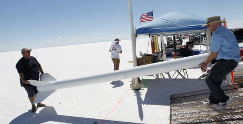 Al Hartmann     The Salt Lake Tribune Mitch Adamson, left, gets help unloading his NASA replica rocket from Jim Buchmiller as they set up on the Bonneville Salt Flats Thursday morning for Hellfire 18, a Utah Rocket Club event in which amateur rocket enthusiasts launch a variety of model rockets up to three miles in the air.