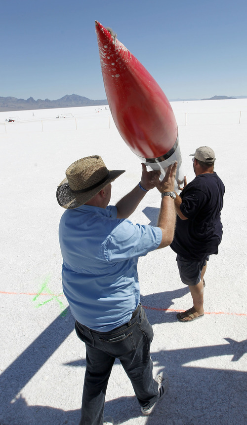 Al Hartmann     The Salt Lake Tribune Mitch Adamson, right, gets help unloading his NASA replica rocket from Jim Buchmiller as they set up on the Bonneville Salt Flats Thursday morning for Hellfire 18, a Utah Rocket Club event in which amateur rocket enthusiasts launch a variety of model rockets up to three miles in the air.