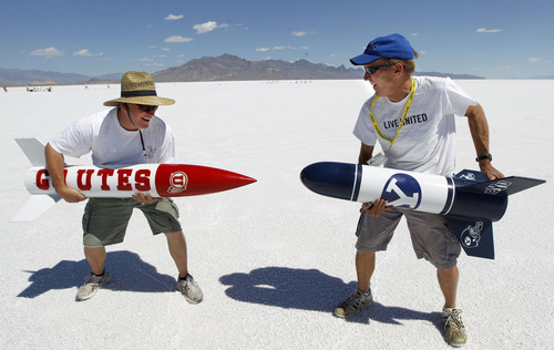 Al Hartmann     The Salt Lake Tribune Alan Ovemoe, left, jokes around in rocket rivalry with friend John Borget on the Bonneville Salt Flats Thursday morning for Hellfire 18, a Utah Rocket Club event in which amateur rocket enthusiasts launch a variety of model rockets up to three miles in the air.  Their U of U-BYU rocket rivalry has been going on for more than 10 years.