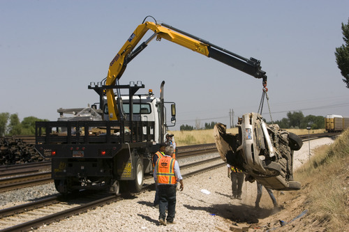 Rick Egan  | The Salt Lake Tribune   Special machinery removes a car that was hit by the FrontRunner this morning, killing the driver, on 4800 South 2700 West in Roy, Friday, August 2, 2013.