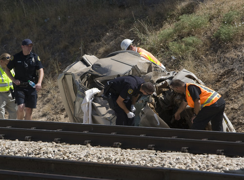 Rick Egan  |  The Salt Lake Tribune Police and FrontRunner officials check out a car that was hit by the train this morning, killing the driver, on 4800 South 2700 West in Roy, on Friday.