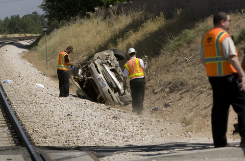 Rick Egan  | The Salt Lake Tribune   FrontRunner officials check out a car that was hit by the train this morning, killing the driver, on 4800 South 2700 West in Roy, Friday, August 2, 2013.