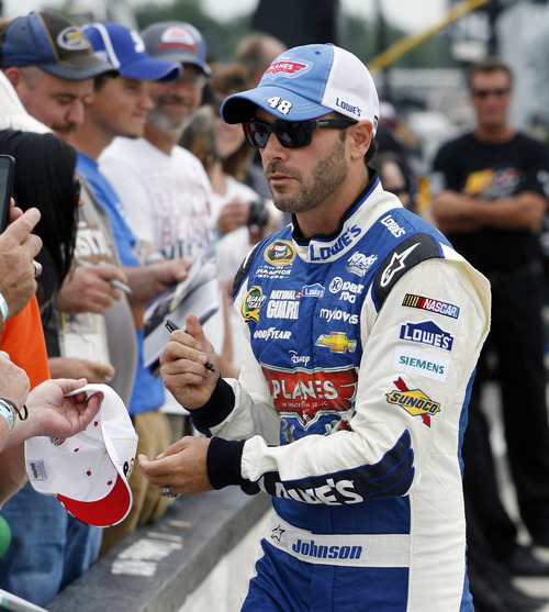 Jimmie Johnson signs autographs along the pits as he waits to qualify for Sunday's NASCAR Sprint Cup Series auto race, Friday Aug. 2, 2013, in Long Pond, Pa.  Johnson qualified on the pole with a speed of 180.654 miles per hour.(AP Photo/Russ Hamilton Jr.)